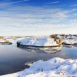 Small rocky islands sprinkled with snow during low tide — Stock Photo #64795613