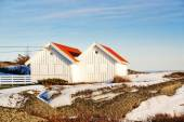 White wooden cottage with red roofs on coast — Stock Photo