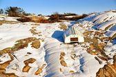 White boat reversed on winter rocky coast — Stock Photo