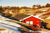 Colorful wooden summer cottage over winter coast — Stock Photo