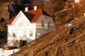Norwegian white wooden house among rocks — Stock Photo