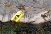 Small yellow boat moored to a rock — Stock Photo