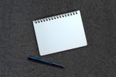 Notebook and pen on asphalt texture — Stockfoto