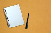 Defter ve kalem sarı karton üzerine — Stok fotoğraf