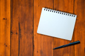 Notebook and pen on wood pattern — Stock Photo
