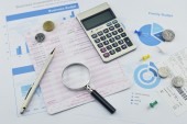 Magnifying glass, pen and coin on graph paper, saving concept — Stock Photo