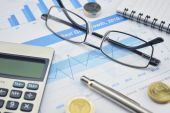 Glasses, calculator and coin on financial chart and graph, accou — Stock Photo