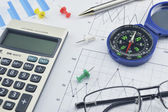 Blue compass, calculator, pen and glasses on graph paper, succes — Stock Photo