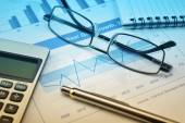 Glasses, pen and calculator on financial chart and graph — Stock Photo