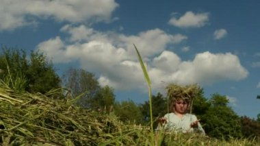 Fair-haired daughter of a farmer weaves a wreath made of straw — Stock Video