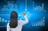 Working women hand drawing business graph — Stockfoto