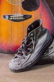 Ahşap zemin üzerinde eski spor ayakkabı. — Stok fotoğraf