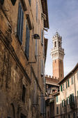 Bell Tower framed by ancient houses — Stock Photo