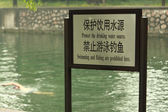 Man is swimming near sign swimming forbidden — Stock Photo