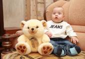 Baby with big blue eyes sit next to teddy bear — Stock Photo