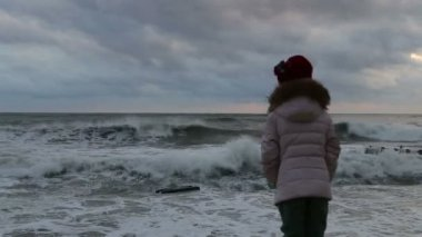 Little girl in inclement weather is on the pier and watching the storm — Stock Video