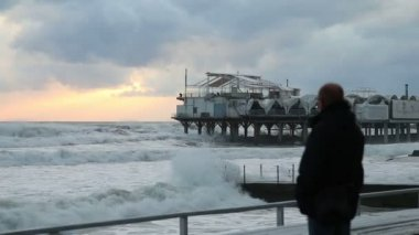 The man in inclement weather is on the shore and looks at the storm. In the background of a restaurant by the sea. Sochi — Stock Video