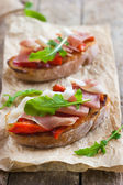 Bruschetta with roasted peppers, prosciutto and arugula — Stock Photo
