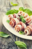 Prosciutto with basil on a white plate — Stock Photo
