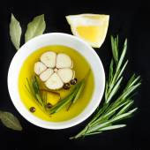 Bowl with olive oil, garlic, ppeppercorn  and rosemary, top view — Stock Photo