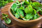 Fresh chard leaves in wooden bowl — Stock Photo