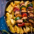 Grilled meat and vegetable kebabs and baked potatoes on pan — Stock Photo #62579805