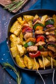Grilled meat and vegetable kebabs and baked potatoes on pan — Stock Photo