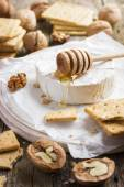 Camembert cheese with crackers, nuts and honey — Stock Photo