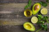 Food background with fresh organic avocado, lime, parsley and olive oil — Stock Photo