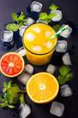 Fresh orange juice on dark background — Stock Photo