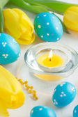 Easter eggs and tulips on white background, selective focus — Stock Photo