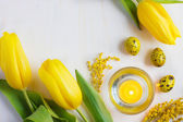 Easter background with candle, yellow eggs  and tulips, top view — Stock Photo