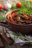 Beef with red bean and vegetables in pot on rustic background — Stock Photo