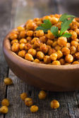 Roasted  spicy chickpeas on rustic background — Stock Photo