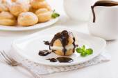 Profiteroles and chocolate sauce — Stock Photo