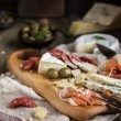 Appetizers. Various types of cheese, salami and prosciutto on  w — Stock Photo #78461770