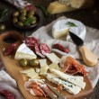 Appetizers. Various types of cheese, salami and prosciutto on  w — Stock Photo #78462244