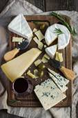 Assortment of various types of cheese on wooden board — Stock Photo