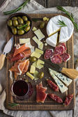 Assortment of various types of cheese and meat on wooden board — Stock Photo