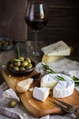 Camembert cheese with rosemary and olives — Stock Photo
