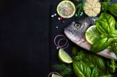 Fresh raw dorado fish with spices and herbs — Stock Photo