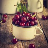 Fresh cherries in enamel mug — Stock Photo