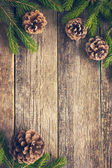 Fir branches and pine cones on wooden background — Stock Photo