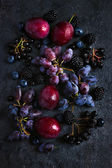 Fresh dark fruits and berries on black background. — Stock Photo