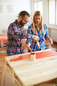 Young couple painting furniture at home — Stock Photo