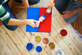 Couple painting furniture in red and blue colour — Stock Photo