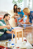 Young couple painting furniture at home — Fotografia Stock