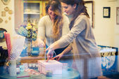 Two women packing gifts — Stock Photo