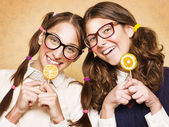 Young female nerds with lollypops — Stock Photo