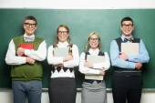 Four nerds in front of blackboard — Stock Photo